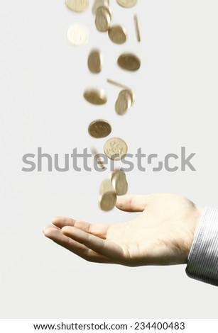 Coing falling out of the sky with hand catching them. - stock photo