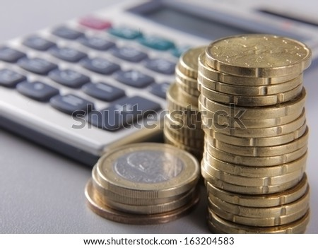 coins and calculator - stock photo