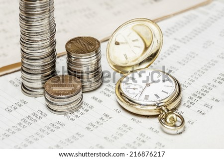 Coins and clock on  a data table  - stock photo