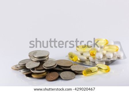 coins and pills on white background. The increase in drug prices, the rising cost of pills, inflation, crisis, isolated - stock photo