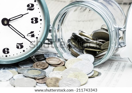 Coins, clock and open glass jar on  a data table - stock photo