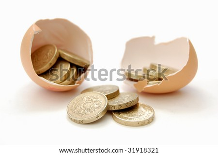 Coins emerge from cracked egg - stock photo