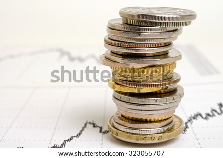 Coins from different countries, stacked in the financial schedule. - stock photo