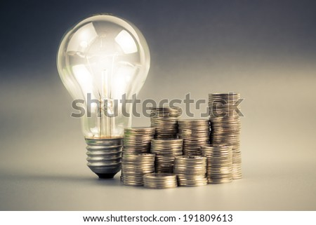 Coins heap and light bulb - stock photo