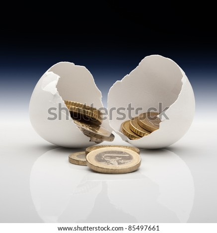 Coins in broken eggshell. Conceptual image for prosperity, luck, happiness. - stock photo
