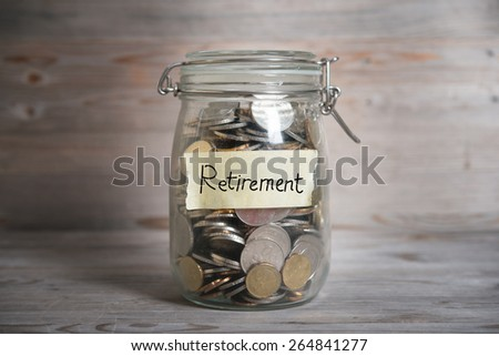 Coins in glass jar with retirement label, financial concept. Vintage wooden background with dramatic light. - stock photo