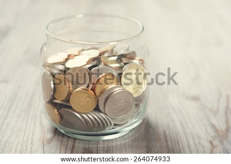 Coins in glass money jar, on wooden background. - stock photo