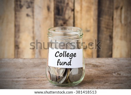 Coins in glass money jar with college fund label, financial concept. Vintage wooden background - stock photo