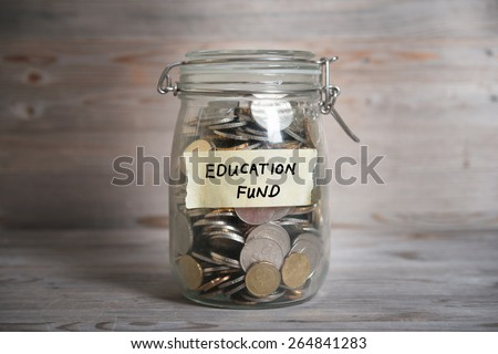 Coins in glass money jar with education fund label, financial concept. Vintage wooden background with dramatic light. - stock photo