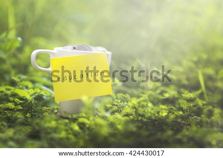 Coins in glass money mug with education label, blurred grass view at background. Financial concept. - stock photo