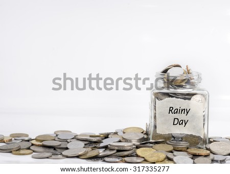 coins in jar with rainy day label in isolated white background; financial concept - stock photo