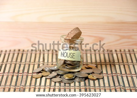 Coins in money jar,writing HOUSE with wooden pallet background. Selective focus with shallow depth of field. House Saving Concept. - stock photo