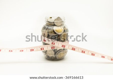 Coins in piggy bank and tape measure around the waist - stock photo