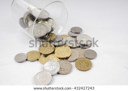 Coins in the glass isolated on white table. Business concept. DOF and copy space.  - stock photo