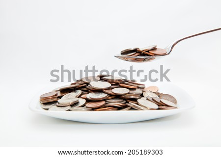 Coins on a plate, and a spoon full of coins on a white background  - stock photo