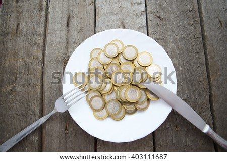 Coins on a plate with fork and knife on wooden table - stock photo