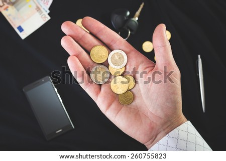 coins on the man's palm on a black background - stock photo