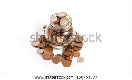 coins overflowing from money jar isolated on wite background - stock photo
