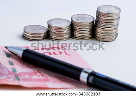 Coins setup in line graph put beside banknote. Put a pen on money, financial accounting concept. - stock photo