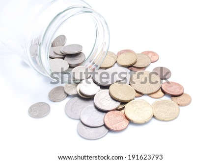 Coins Spilling from a Jar - stock photo