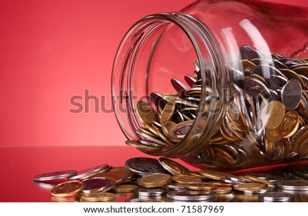coins spilling from a money jar on red background - stock photo