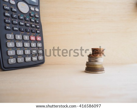 Coins tower and calculator on wood background  - stock photo