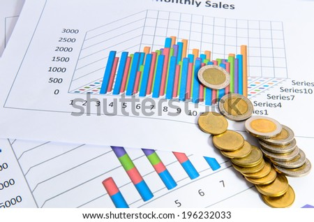 Coins with business data charts or graphs - stock photo
