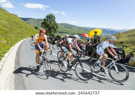 COL DE PEYRESOURDE,FRANCE- JUL 23:Unidentified amateur cyclists riding on the road to Col de Peyresourde before the apparition of the peloton during the stage 17 of Le Tour de France on 23 July 2014. - stock photo