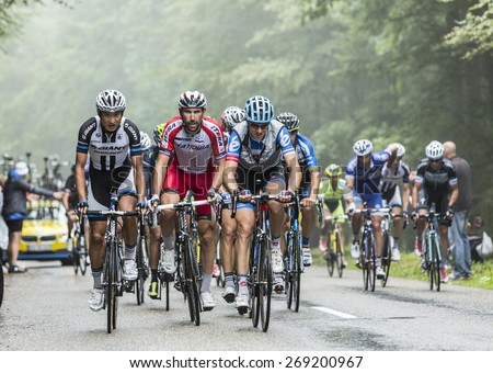 COL DU PLATZERWASEL,FRANCE - JUL 14: The peloton on the climbing road to mountain pass Platzerwasel in Vosges Mountains, during Le Tour de France on July 14 2014 - stock photo