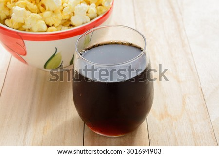 Cola and popcorn on wooden table. - stock photo