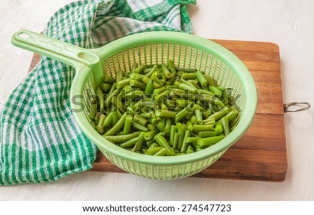 Colander with leguminous of green raw beans on the cutting board on the kitchen table - stock photo