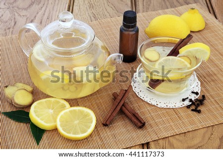 Cold and flu alternative medicine with hot lemon, honey and spice drink in a cup and glass teapot with fresh fruit and aromatherapy bottle on bamboo over oak background. - stock photo