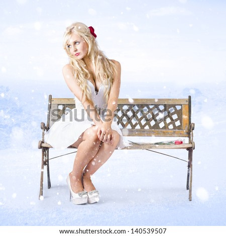 Cold and lonely winter girl sitting all alone on park bench under falling snow with a single red rose by her side. Heartbroken - stock photo