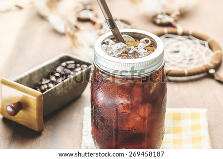 Cold arabica coffee with iced in vintage jar. Photo in vintage color tone style. - stock photo