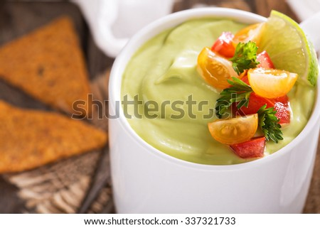 Cold avocado soup with tomato and herb salsa and tortilla chips - stock photo