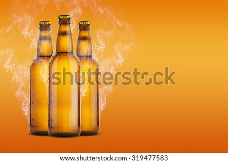 Cold Beer Bottles with drops, frost and vapour on orange Background - stock photo