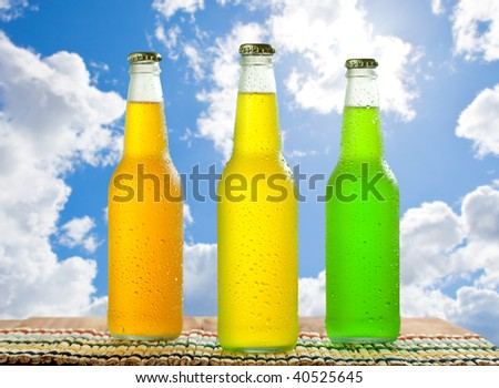 Cold beverages in glass bottles on wooden table top with nice blue sky in the background - stock photo