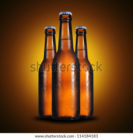 Cold 3 bottles of light beer on yellow background - stock photo