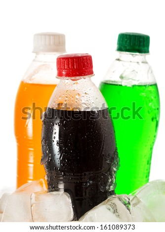 cold bottles of soda in ice on white background - stock photo
