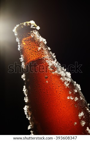 Cold brown bottle of beer with water droplets, ice and light beam on top over black background - stock photo