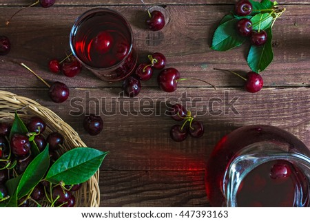 cold cherry juice in a glass and pitcher with cherries inside on wooden table with ripe berries in wicker basket. top view - stock photo