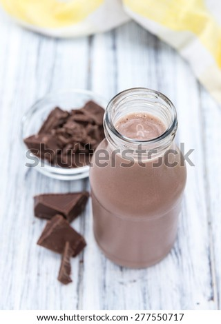 Cold Chocolate Milk drink (close-up shot) on wooden background - stock photo