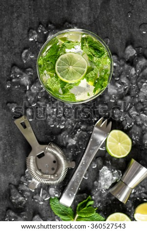 Cold cocktail with lime, mint, ice. Drink making tools and ingredients. Top view. Selective focus - stock photo
