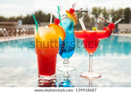 Cold cocktails on the background of the pool - stock photo