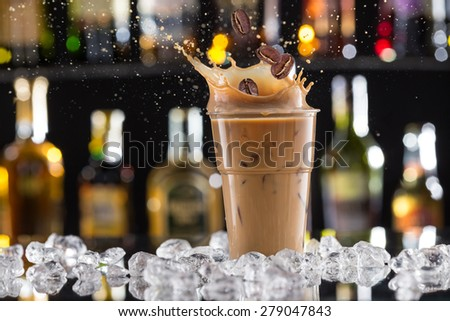 Cold coffee drink with ice, beans and splash, close-up. - stock photo