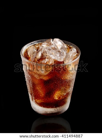 Cold cola with ice in a glass on a black background - stock photo