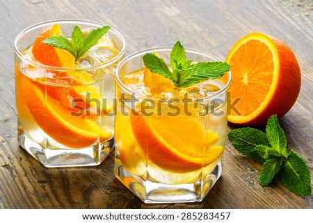 Cold drinks with ice and mint. Orange cocktail on rustic wooden table - stock photo