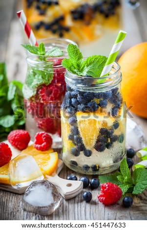 Cold drinks with straws - blueberry with orange slices and raspberries summer refreshing cocktails. - stock photo