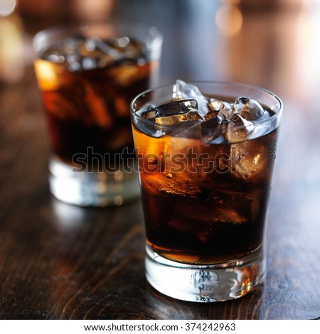 cold fizzy cola soda with ice in glass cup - stock photo
