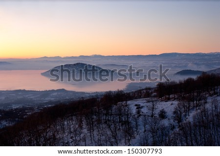 Cold foggy sunrise in the snowbound mountains of Greece, Kastoria. - stock photo